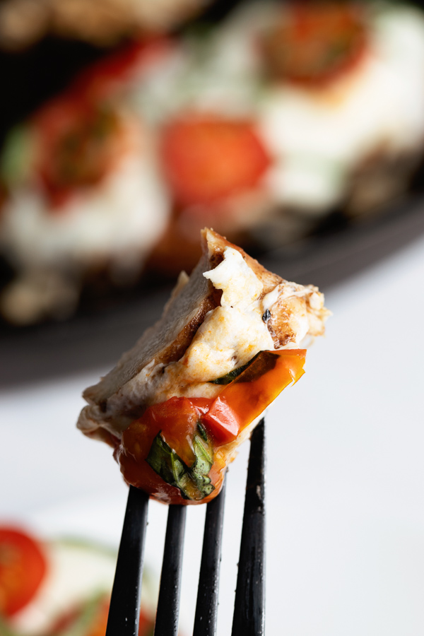 Freshly prepared Grilled Chicken Caprese with Balsamic reduction on a fork in front of a cast iron grill pan with another prepared chicken breast.