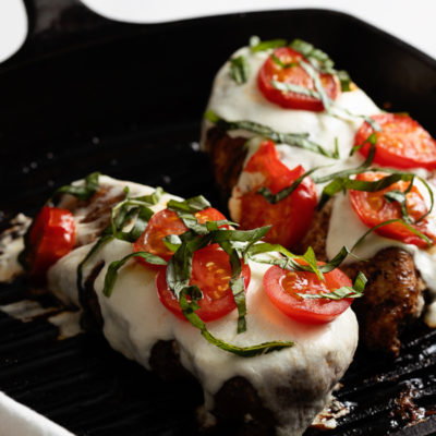 Cast Iron Grill Pan with two finished grilled chicken caprese chicken breasts sitting atop a white background.