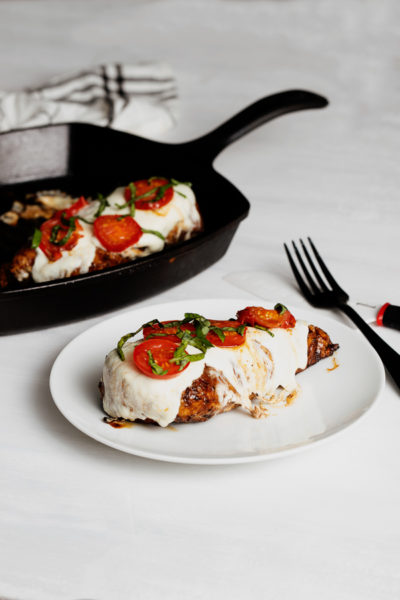 Easy Grilled Chicken Caprese in a grill cast iron pan and white plate. Balsamic glazed chicken topped with mozzarella cheese, tomatoes and fresh basil.