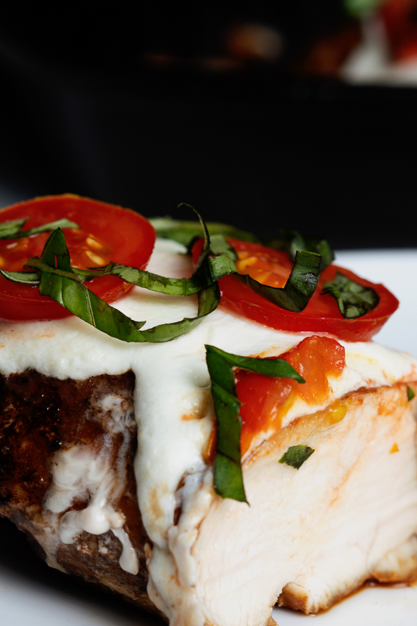A close-up view of fresh basil and small red tomatoes atop a bed of melted Mozzarella cheese, covering a balsamic glazed chicken breast.