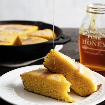 sliced cornbread on white plate with drizzled honey