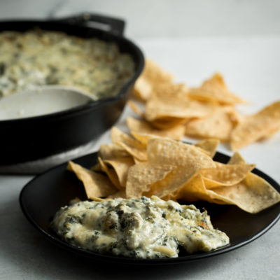 Spinach and artichoke dip in a cast iron skillet with chips on a black plate