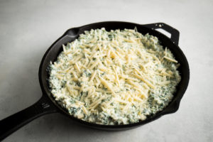 Add extra Parmesan cheese to spinach artichoke dip before baking in the oven.