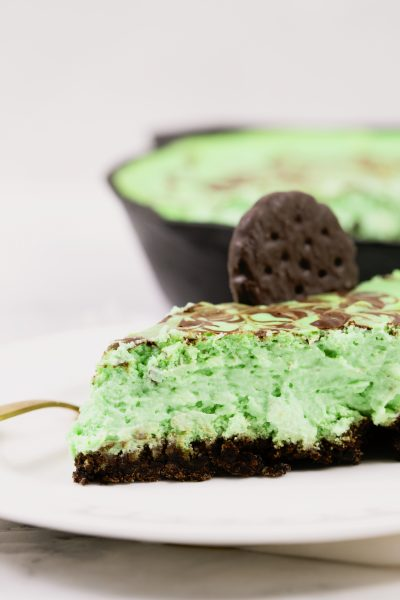 slice of thin mint cheesecake on white plate with thin mint cookie on top