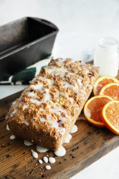 whole loaf of cranberry bread with orange slices and covered in glaze on wooden cutting board