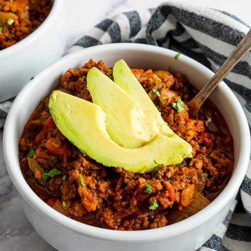 white bowl full of spicy chipotle chili topped with sliced avocados