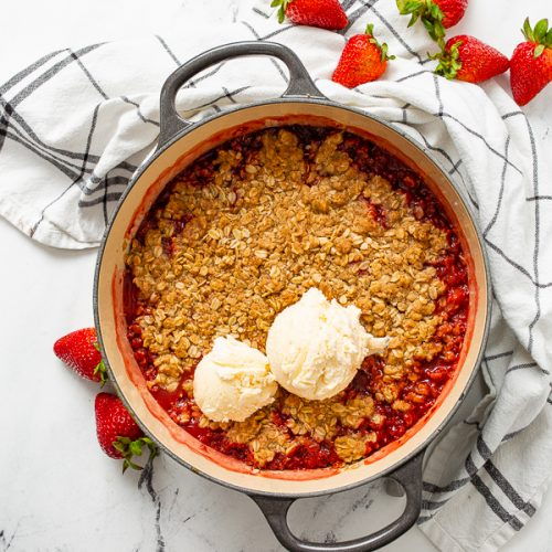 dutch oven strawberry rhubarb crisp with a scoop of ice cream on top