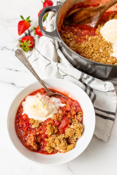 white bowl of dutch oven strawberry rhubarb crisp