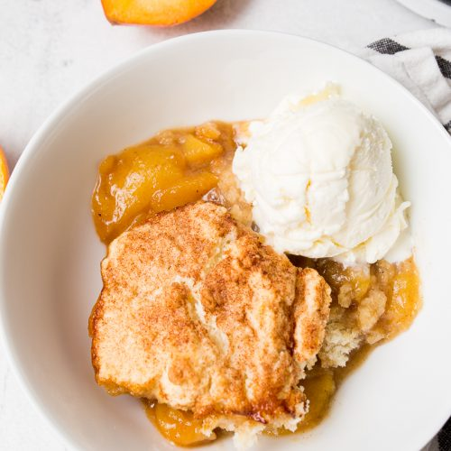 white bowl full of dutch oven peach cobbler