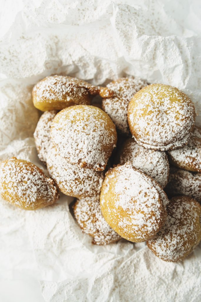 Finished deep fried oreos dusted with powdered cinnamon sugar in a basket with white parchment paper.