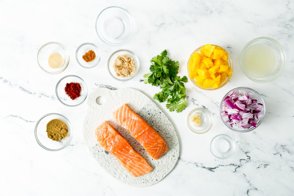 Overhead image of the ingredients required for blackened salmon with mango salsa: two salmon filets, salt, brown sugar, cayenne, onion powder, smoked paprika, cumin, cilantro, mango, purple onion, lime juice, garlic, and salt. All in glass bowls on a white marble countertop.