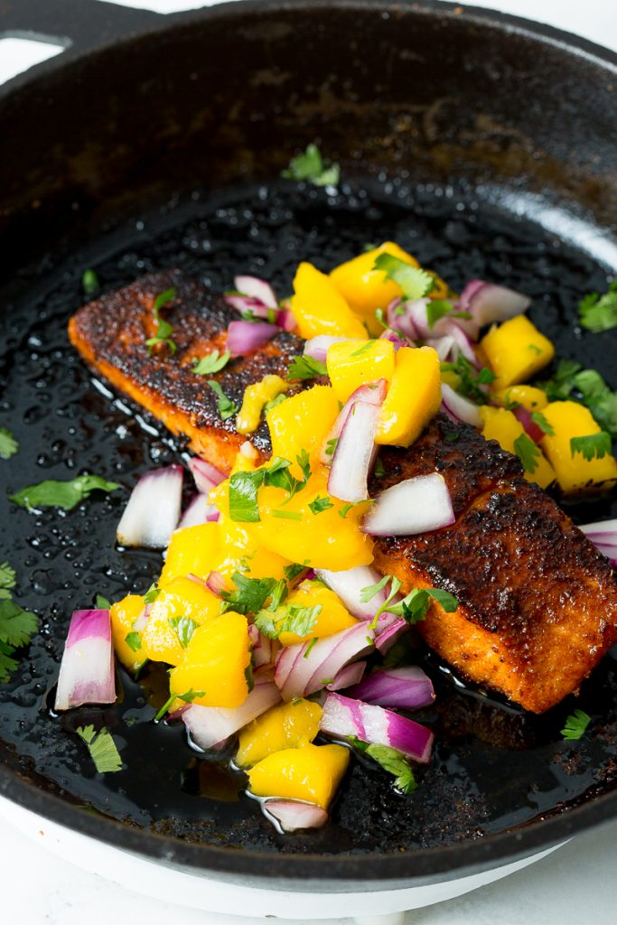 A close up image of blackened salmon topped with mango salsa in a cast iron skillet.