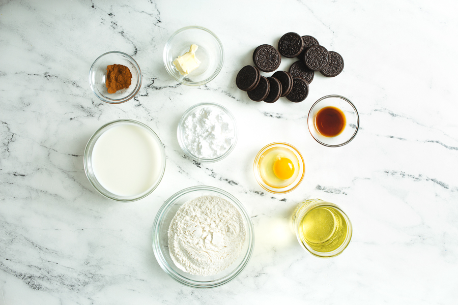 Ingredients for deep fried oreos laid out in glass bowls on a white marble countertop: cinnamon, butter, Oreos, milk, powdered sugar, butter, vanilla extract, pancake mix, and peanut oil.