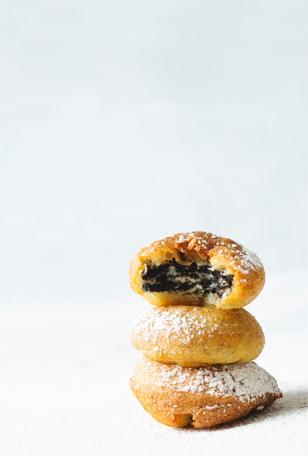 Three homemade deep fried oreos dusted with cinnamon powdered sugar are stacked on top of each other with a white background. The top deep fried oreo has a single bite taken out of it, exposing the inside of this favorite fair food.