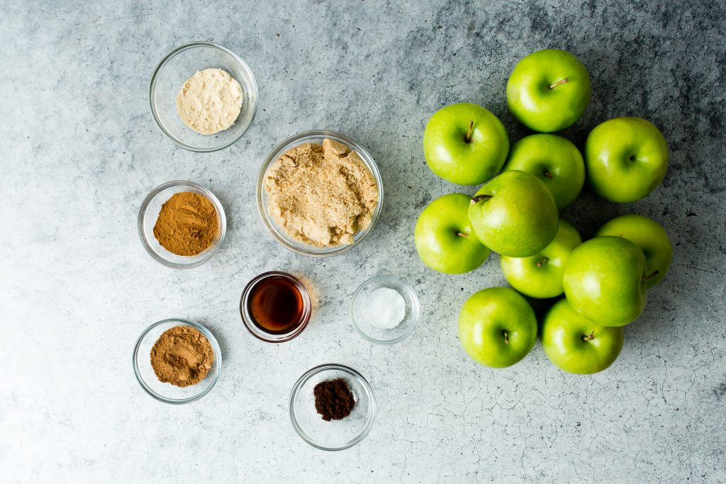 Ingredients for dutch oven apple butter are pictured on a grey/blue background. Ingredients are granny smith apples, granulated maple, brown sugar, cinnamon, nutmeg, vanilla extract, salt, and ground cloves.