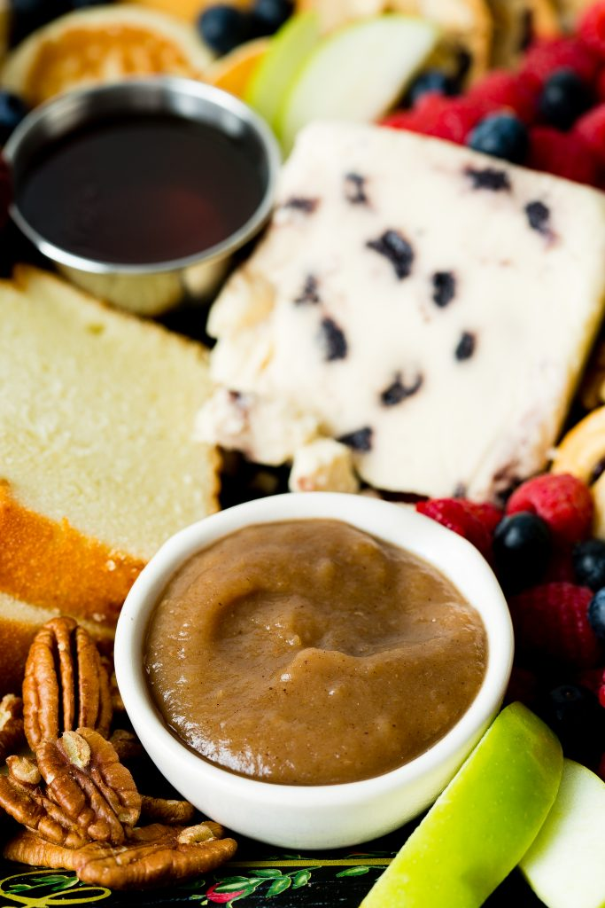 Apple butter as part of a fall breakfast board with cheese, pound cake, nuts and berries.