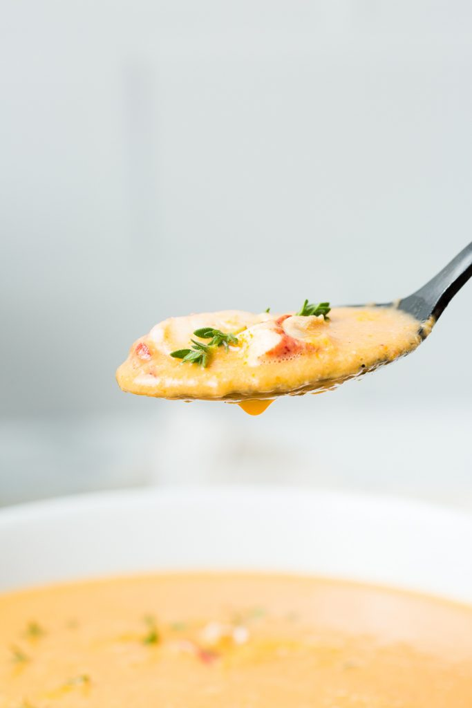 A black spoonful of lobster bisque topped with fresh lobster meat and fresh thyme in the foreground hovers over a white bowl of lobster bisque in the background.