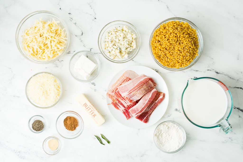 Image: An overhead view of the ingredients for this Dutch Oven Mac and Cheese individually placed in glass bowls and a white plate. The ingredients include: Cheddar cheese, blue cheese, gruyere cheese, cream cheese, elbow macaroni, bacon, butter, fresh sage, pepper, nutmeg, garlic powder, flour, and whole milk.