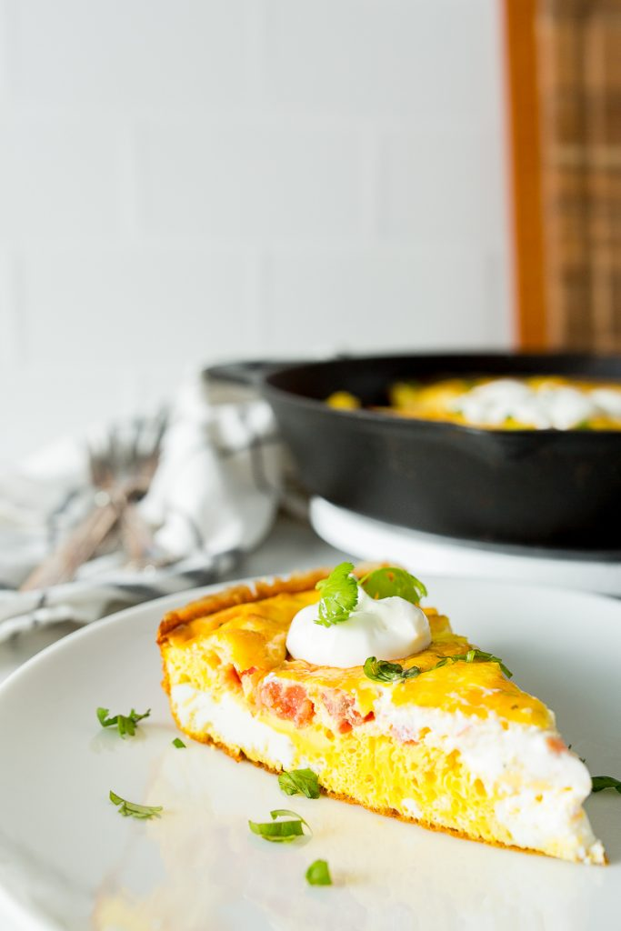 A close up image of a single slice of mexican frittata. Slice is presented on a white plate with a dollop of sour cream and fresh cilantro. The cast iron skillet with the remainder of the frittata is pictured out of focus in the background.