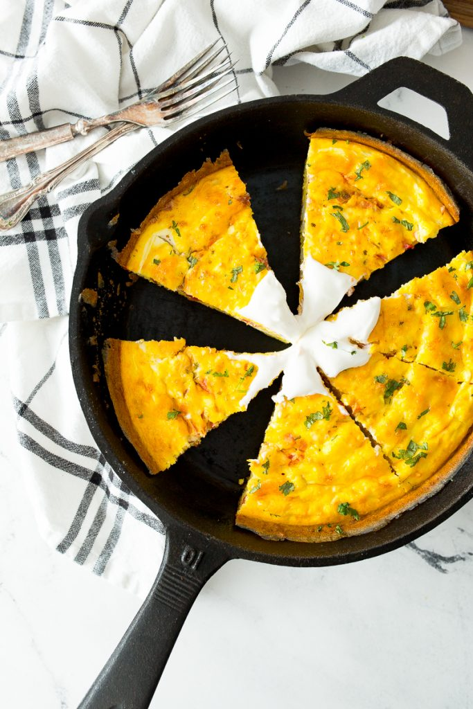 A number 10 cast iron skillet holds slices of a mexican frittata with sour cream on a white marble countertop. The skillet sits on a blue and white plaid hand towel with two antique forks in the corner. View of the skillet is from overhead.