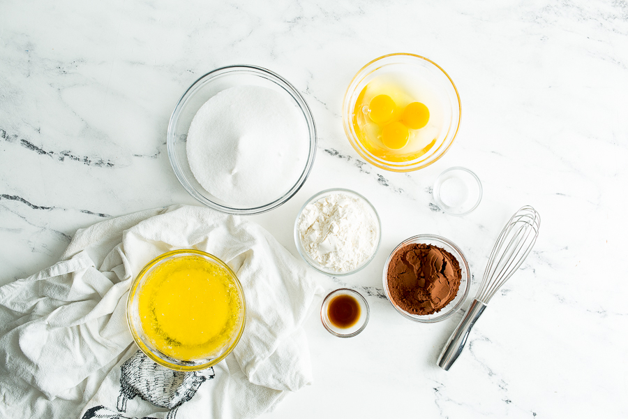Overhead image of the 7 ingredients used to create basic skillet brownies. Ingredients are in clear glass bowls on a white tabletop. Ingredients are: sugar, eggs, flour, salt, butter, vanilla extract, and cocoa powder. A whisk and white linen are also pictured.