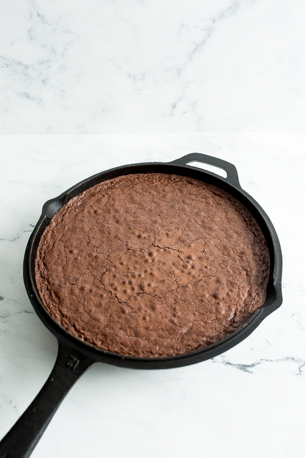 Angled photo of the number 12 cast iron skillet with the finished baked brownies, uncut, on white marble countertop.