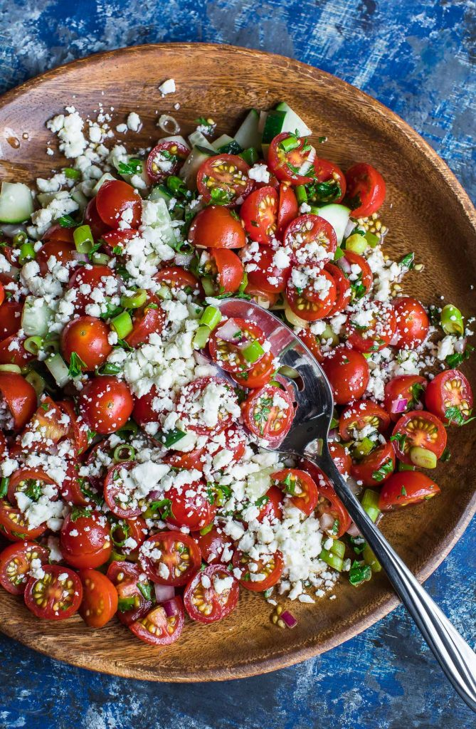 A clickable image of cherry tomato salad in a large wooden bowl with a silver spoon.