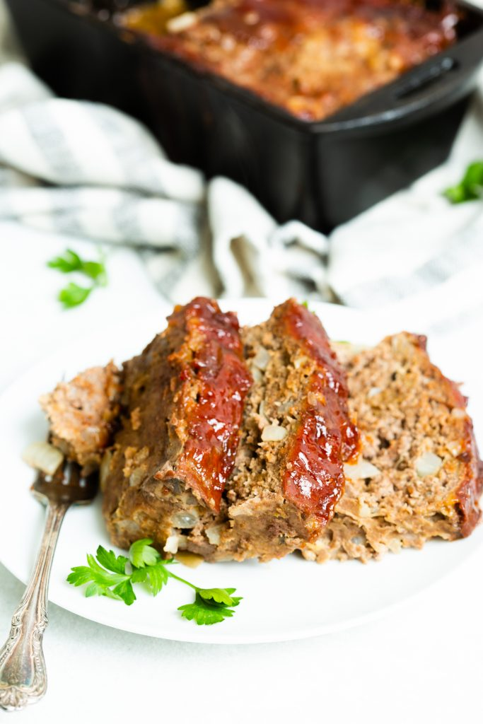 Image of: three slices of meatloaf with ketchup glaze on a white plate and a cast iron loaf pan in the background.