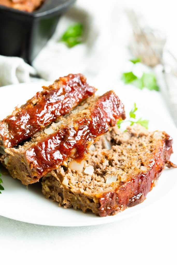 Image of: three slices of meatloaf on a white plate and cast iron loaf pan in the background.