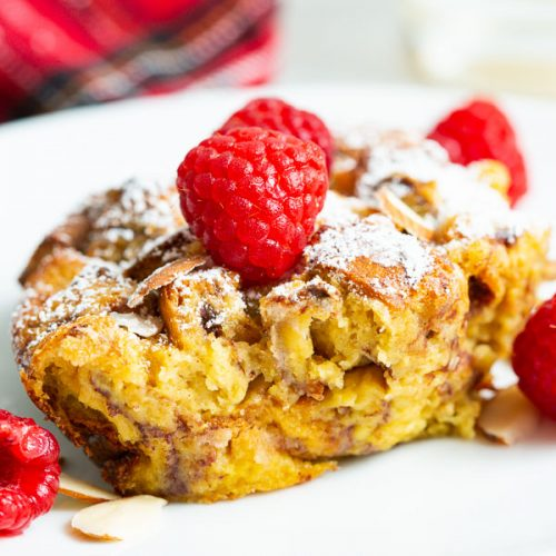 A close up, side view of eggnog french toast casserole on a white plate topped with red raspberries.
