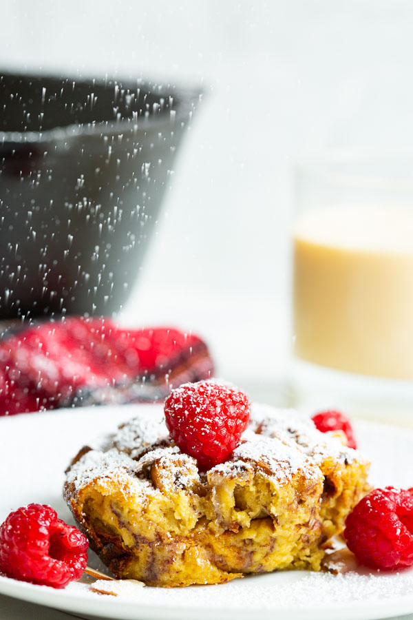A close up, side image of eggnog french toast casserole being dusted with powdered sugar, eggnog and skillet in the background.
