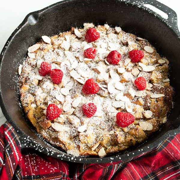 Eggnog french toast casserole in a cast iron 12 inch skillet dusted with powdered sugar and dotted with fresh raspberries