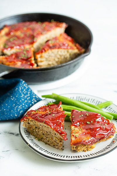 Ground Turkey Meatloaf served with green beans along side a skillet of sliced meatloaf.