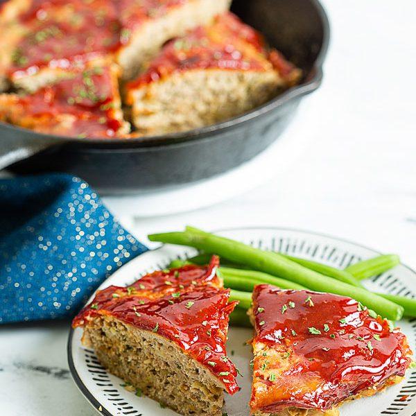 Ground Turkey Meatloaf served with green beans along side a skillet of sliced meatloaf.