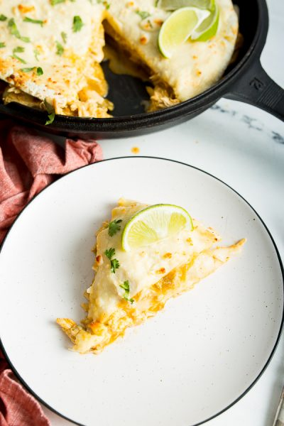 A close up image of green enchilada lasagna on a plate topped with cilantro and lime wedge, with a cast iron skillet in the background.