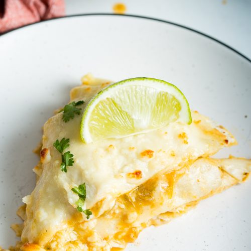 A 45* angle image of green enchilada lasagna on a plate topped with lime and cilantro.