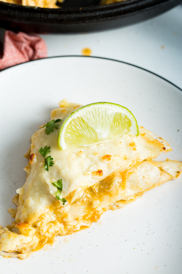 An overhead shot of Green Chicken Enchilada Lasagna topped with cilantro and a lime wedge on a white plate with a black rim.