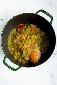 An inside view of a green dutch oven with green chicken enchilada mixture in process of cooking.