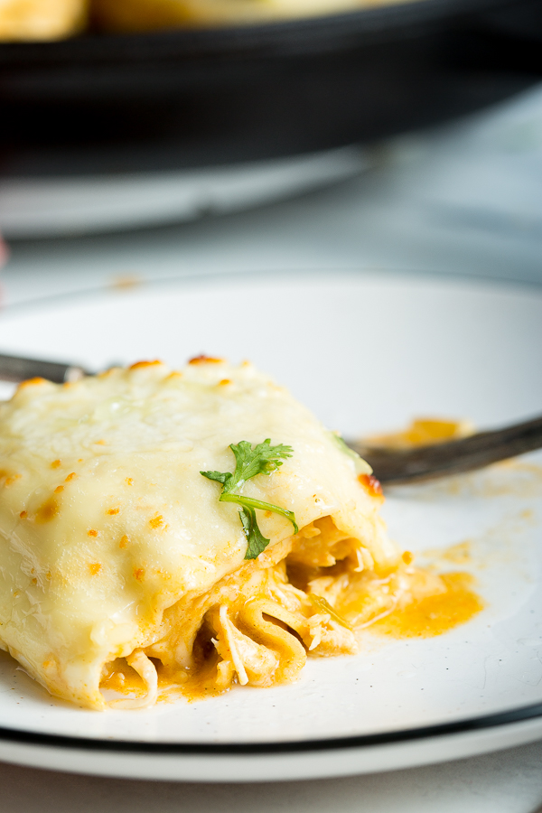 A close up image of white chicken tortilla lasagna on a black rimmed white plate with black fork and skillet in the background.