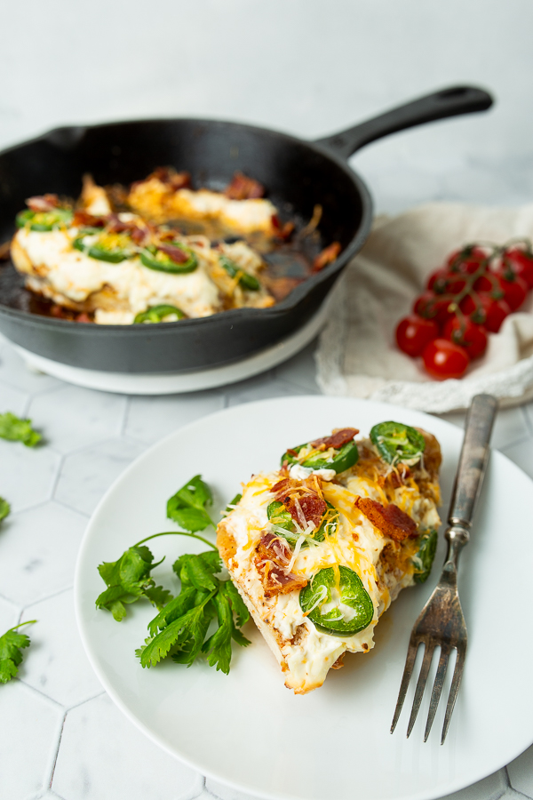 Image of baked jalapeno popper chicken on a white plate with a cast iron skillet in the background.