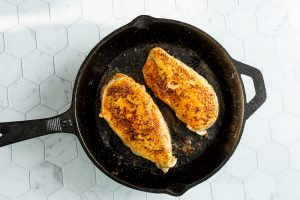 Seared chicken breast in a 10 inch cast iron skillet.