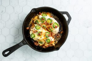 Overhead image of a 10 inch cast iron skillet with jalapeno popper chicken breast topped with cheese and bacon.