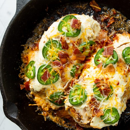 Overhead image of jalapeno popper chicken breast in a cast iron skillet.