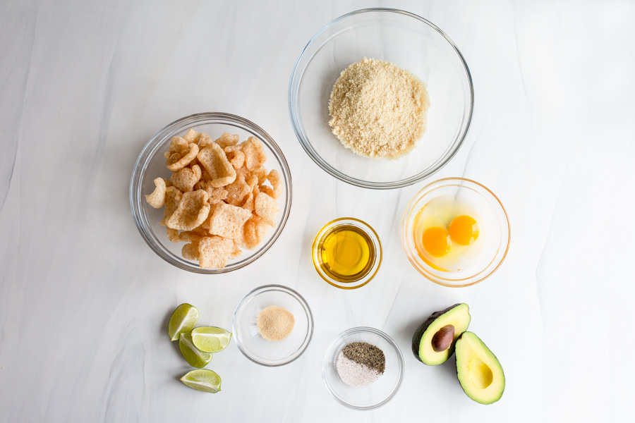 Ingredients for keto, low-carb avocado french fries in individual bowls on a white background.