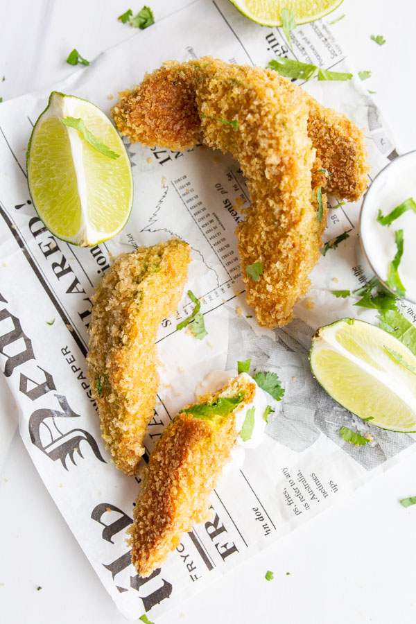 An overhead image of keto avocado fries on a newspaper with cilantro, lime, and dipping sauce.