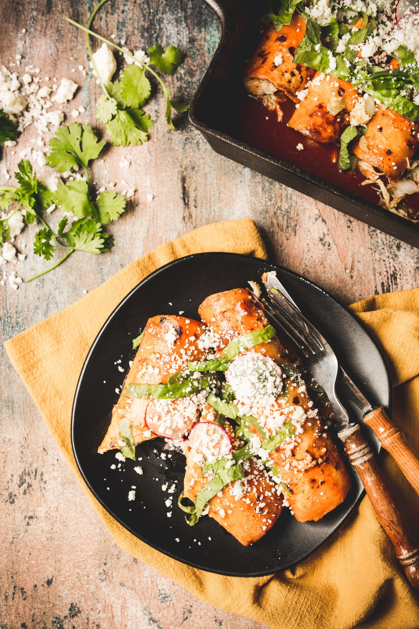 Overhead image of red chicken enchiladas on a black serving plate topped with radishes, lettuce, and cotija cheese.
