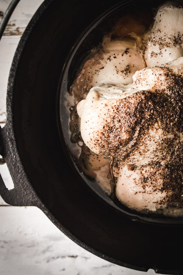 Overhead image of chicken breasts and chicken broth in a dutch oven.