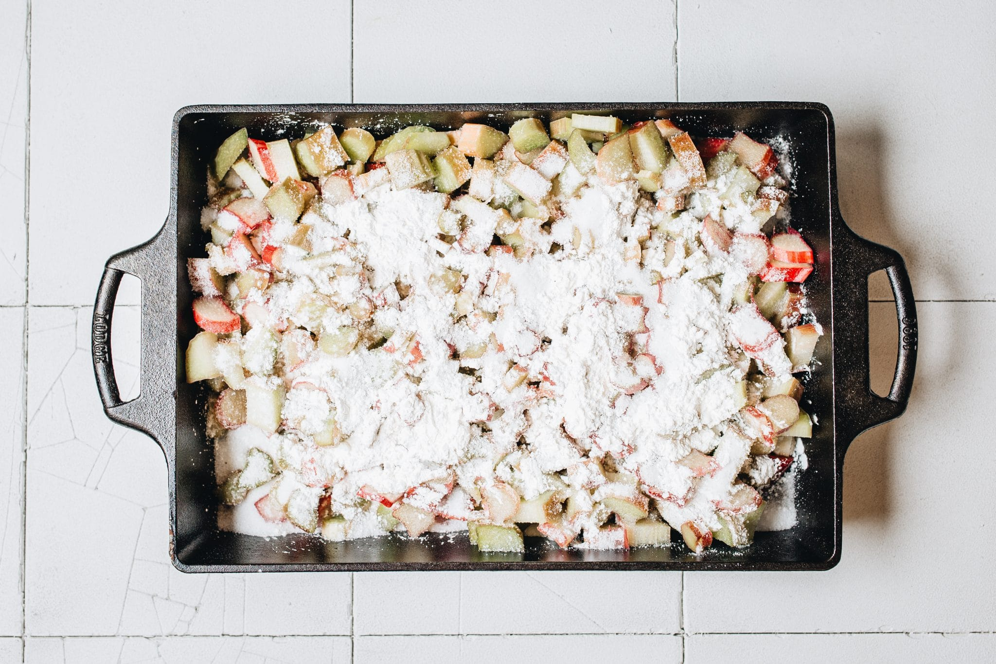 Overhead image of rhubarb cobbler ingredients in a cast iron casserole dish.