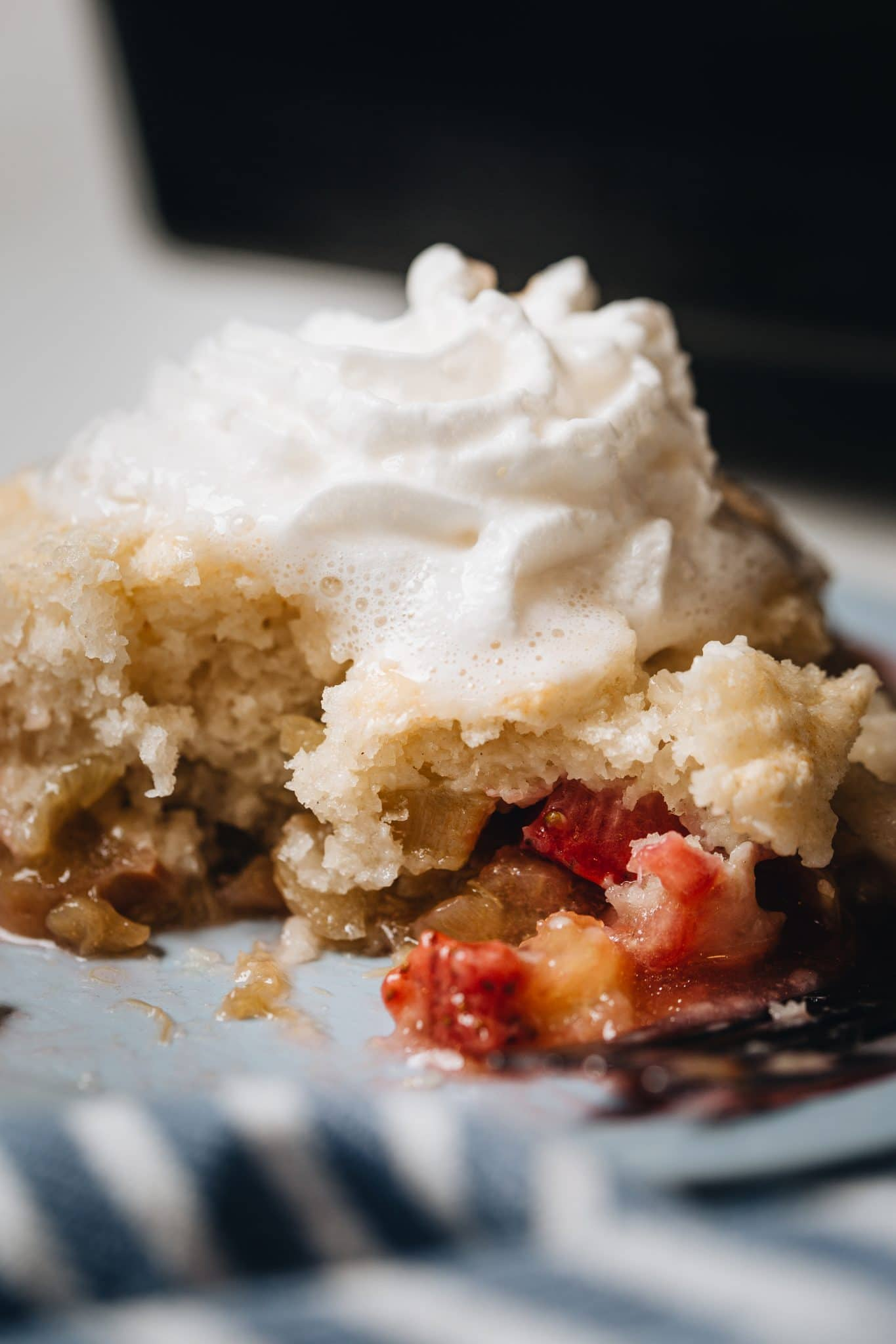 Side image of rhubarb cobbler topped with whipped cream.