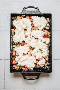 Overhead image of rhubarb cobbler in a cast iron casserole dish.